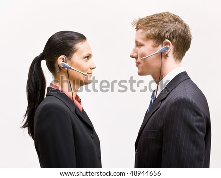 Business people in headsets standing face to face - stock photo
