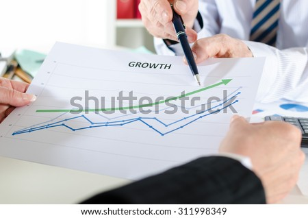 Business people in meeting analyzing financial results - stock photo