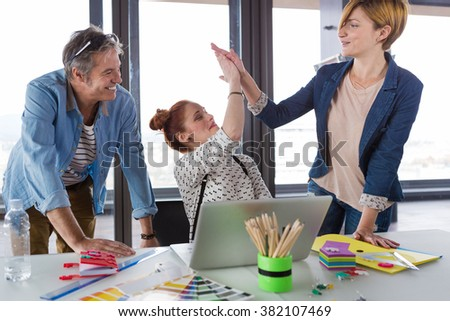 Business people in modern office celebrating good business results. - stock photo