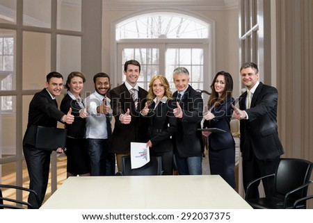 Business people in modern office show thumbs up. Clerks at the meeting. - stock photo