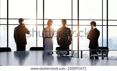 business people in office and looking to window