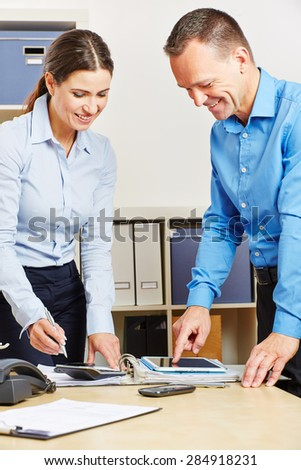 Business people in office planning financing with a tablet computer - stock photo