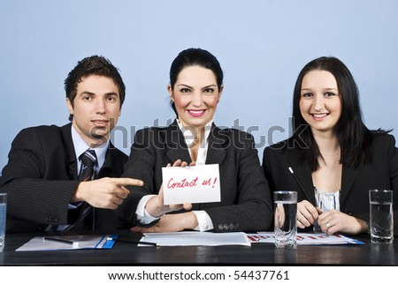 Business people in office showing a paper with contact us written - stock photo