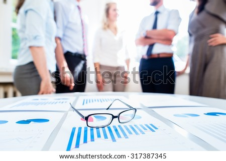 Business people in office with financial data on desk ready for analysis - stock photo