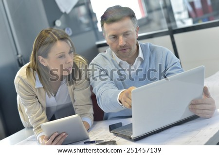 Business people in office working on laptop and tablet