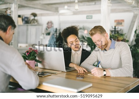 Business people in smart casual wear are discussing affairs, using a laptop, drinking coffee and smiling while co-working in the cafe