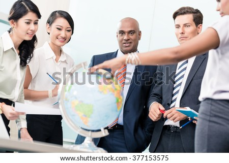 Business people in Strategy meeting discussing new markets looking at a globe  - stock photo