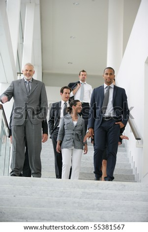 Business people in suit coming down stairs - stock photo