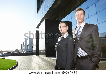Business people in suits with business building - stock photo