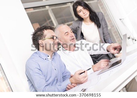 Business people interacting, discussing and sharing ideas in bright modern office. Selective focus on man in the middle - stock photo
