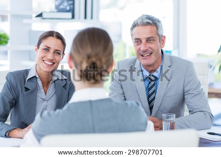 Business people interviewing young businesswoman in office - stock photo