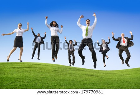 Business People Jumping On a Green Hill - stock photo
