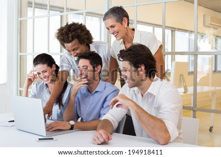 Business people laugh while looking at laptop in the office - stock photo