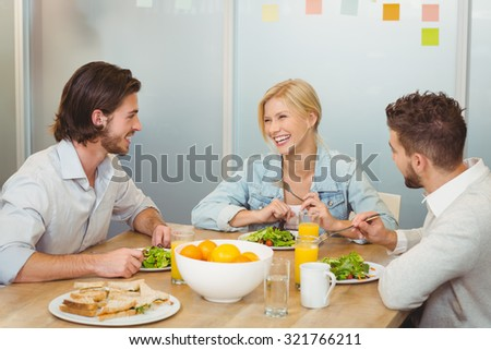 Business people laughing during lunch in creative office