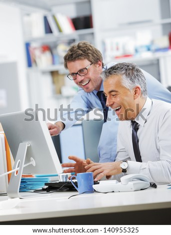 Business people laughing in front of a screen computer - stock photo