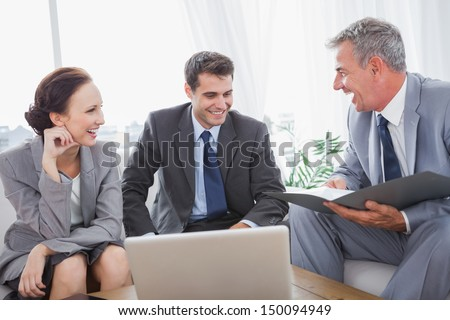 Business people laughing while having a meeting in cosy meeting room - stock photo