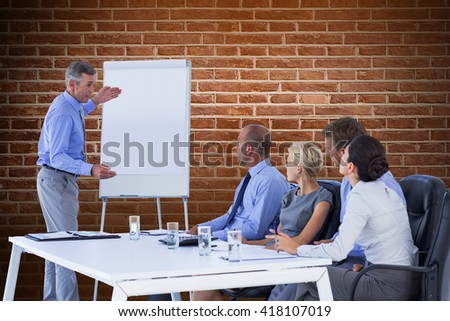 Business people listening during meeting against red brick wall - stock photo