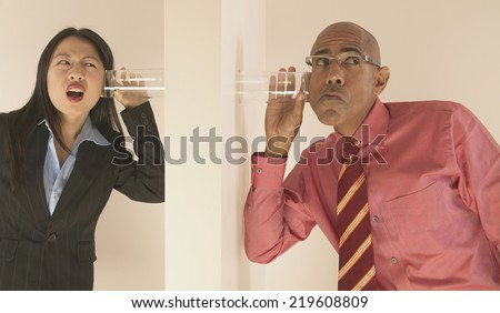 Business people listening through wall with glass to ear - stock photo