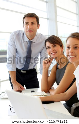 Business people looking at business plan on board - stock photo
