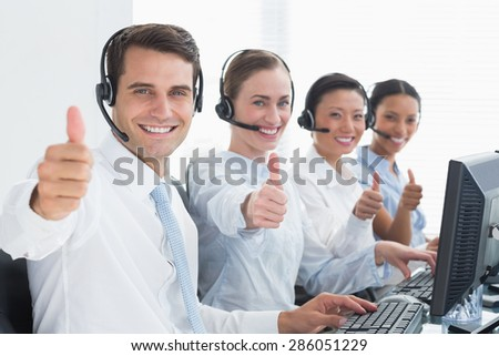 Business people looking at camera with thumbs up in office - stock photo