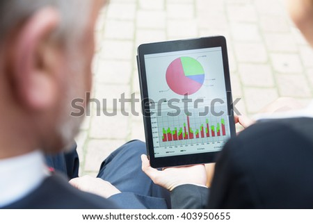 Business people looking at chart and graph on tablet pc