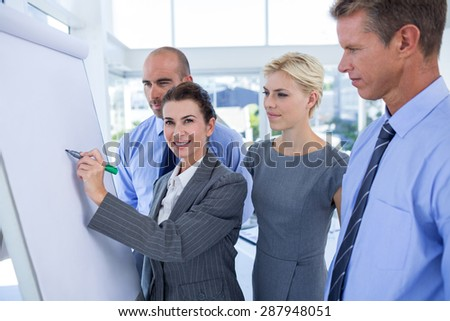 Business people looking at conference board in office - stock photo