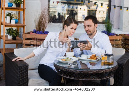 Business people looking at digital tablet in cafe during a meeting - stock photo