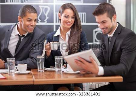 Business people looking at digital tablet in cafffee during a meeting - stock photo