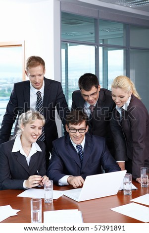 Business people looking at laptop in office - stock photo