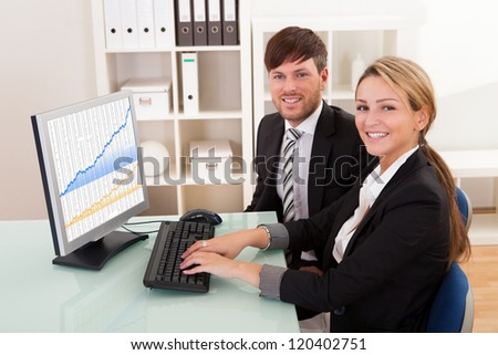 Business people looking at sales growth charts in the office - stock photo