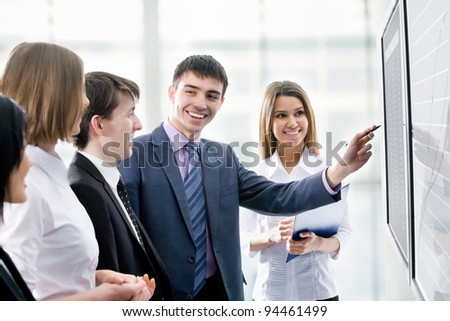 Business people looking at their leader while he explaining something on screen - stock photo