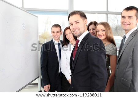Business people looking at their leader while he explaining something on whiteboard - stock photo