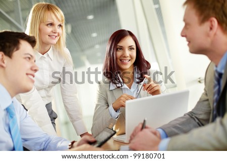 Business people looking at their male colleague approvingly as he has come up with a really good idea - stock photo