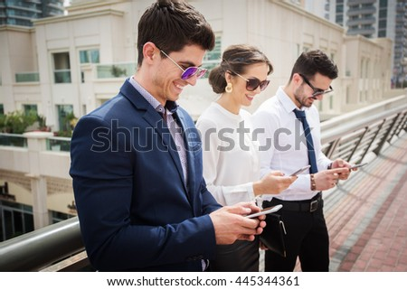 Business people looking at their smart phones. - stock photo