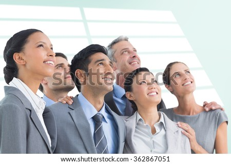 Business people looking up in office against blue vignette background