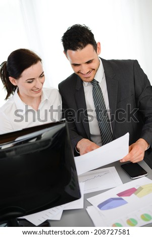 business people man and woman analyzing together company results on paperwork with computer