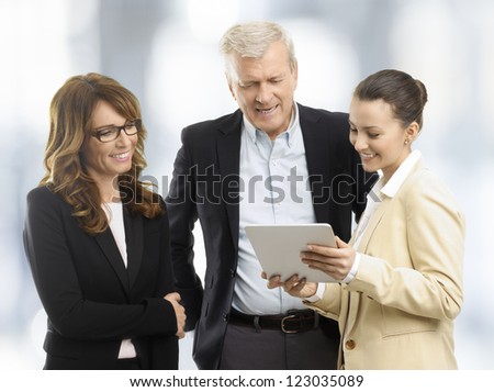 Business People (mature and a young business woman and a businessman) standing in the office and looking at a digital tablet - stock photo
