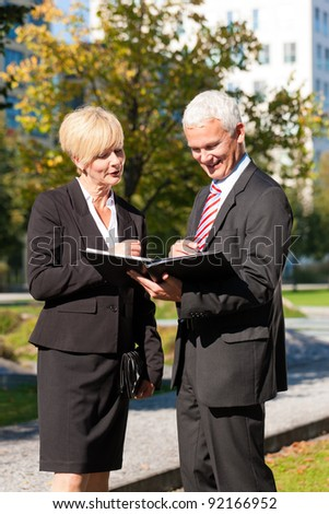 Business people - mature or senior - talking outdoors and discussing a document - stock photo