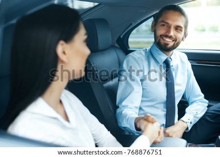 Business People Meeting And Working In Car. Beautiful Smiling Woman And Handsome Businessman In Formal Wear Shaking Hands, Working While Going To Work. High Quality Image.