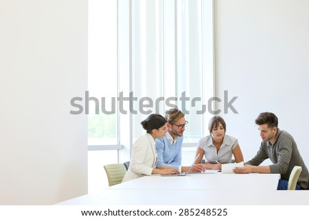 Business people meeting around table in modern space - stock photo