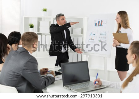 Business people meeting in office to discuss project. Speaker shows the size of profit. Business success concept - stock photo