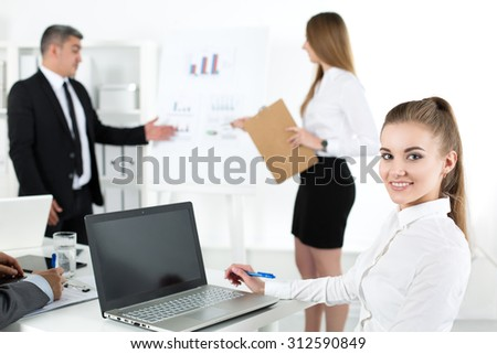 Business people meeting in office to discuss project. Young pretty female office worker looking at camera with her colleagues acting on background. Business meeting and teamwork concept - stock photo