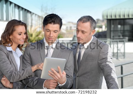Business people meeting outside with electronic tablet - stock photo