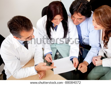 Business people negotiating medical insurance with a group of doctors - stock photo