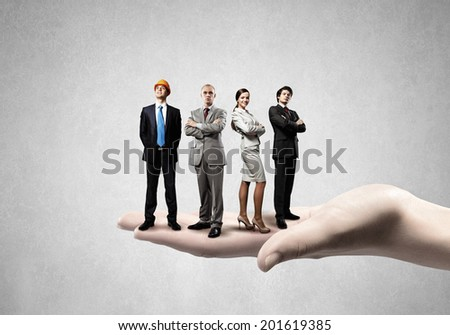 Business people of different professions standing on palm - stock photo