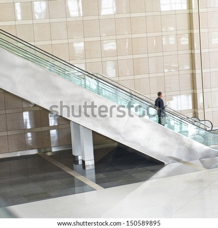 Business people on escalator. Blurred motion - stock photo