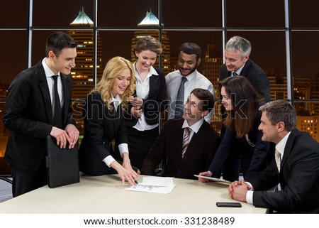 Business people on the background of the night city. Business life. Business people in office of skyscraper. Panoramic view from the window. - stock photo