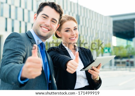 Business people or businessman and businesswoman working outdoor, using pad or tablet computer