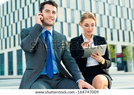 business people or businessman and businesswoman working outdoor, using pad or tablet computer and mobile cell phone - stock photo