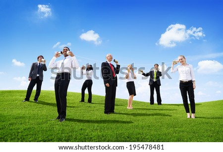 Business People Outdoors Talking Through Tin Can Phone - stock photo